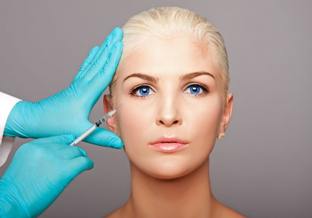 Cosmetic plastic surgeon injecting restylane under eye